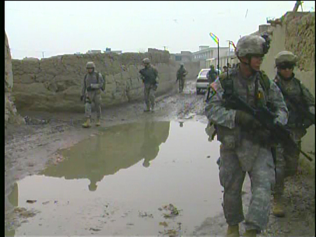 Soldiers walking through mud alley - by: Tim King