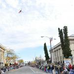 "A U.S. Coast Guard HH-65 ""Dolphin"" helicopter conducts a flyover of 1st Avenue in Albany, Oregon"