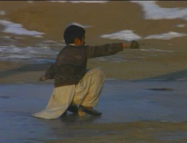 Afghan boy sliding on ice - by: Tim King