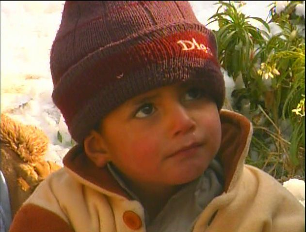 Little Afghan boy in red beanie - by: Tim King