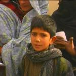 Afghan boy with scarf in med line - by: Tim King