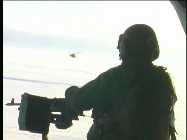 Rear gunner in a CH-47 with Blackhawk over his shoulder - by: Tim King